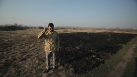 Man stands on the background of burnt grass and grabs his head. Tears hair on his head and regrets indignant angry