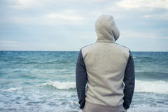Man stands on the beach in a tracksuit with a hood and looking. A man stands on the beach in a tracksuit with a hood and looking at the sea. Cloudy weather Stock Image