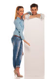 Man stands behind white sign while woman is presenting Royalty Free Stock Photography