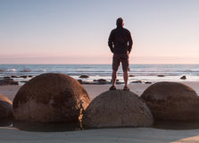 Man stands on a boulder at ocean shore Royalty Free Stock Photography
