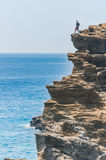 Man stands on cliff above ocean Stock Photography
