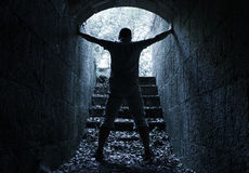 Man stands in dark stone tunnel with glowing end Royalty Free Stock Photography
