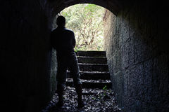 Man stands in dark stone tunnel with glowing end Stock Images