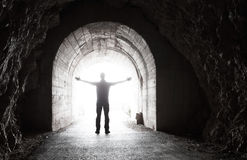 Man stands in dark tunnel with glowing end Royalty Free Stock Photos