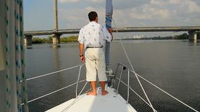 Man stands on deck of yacht. Sailing, yachting, vacation, sport. Stock footage stock video footage