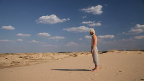 A man stands in the desert. A man stands on the hot sand under the scorching sun in the desert stock footage