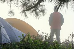 The man stands in the fog at the tent. The man stands in the fog in front of the tent in the morning royalty free stock image