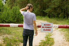Man stands in front of a barrier in the forest Royalty Free Stock Photos