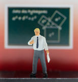 Man stands in front of chalkboard. Plastic puppet man in white shirt and grey trousers. Stock Images