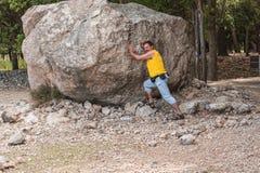 Man stands in front of a large rock. Cope Task. Large boulders, erratic boulder erosion originated in the Serra de Tramuntana in Mallorca Stock Photo