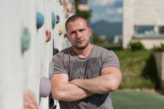 Man Stands In Front Of An Outdoors Climbing Wall Stock Image