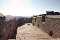 A man stands on the great wall of China. Wall ancient wall of China and a man stands with his hands raised. The main attraction of China royalty free stock photo