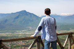 Man stands on high terrace looking to mountains Stock Photo