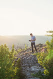 Man stands on a hill and reading a book vertical Stock Photography