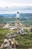 A man stands on a hill among the stones. A beautiful landscape royalty free stock photo