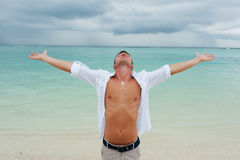 Man stands with his hands raised up on the beach Stock Photography