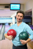 Man stands and holds two balls for bowling Stock Photography