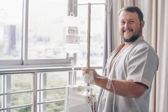 A man stands in a hospital ward and looks out the window. Dropper in a mans hand in a hospital. A man stands in a hospital ward and looks out the window royalty free stock images