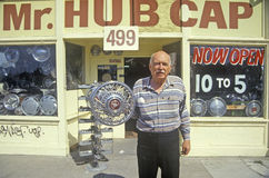Man stands with hub cap in front of �Mr. Hub Cap� shop, San Jose, California stock photography