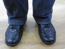 Man stands in jeans and in casual shoes. Man in jeans and everyday shoes. Man in jeans and casual shoes. Male legs in jeans and boots Royalty Free Stock Photo