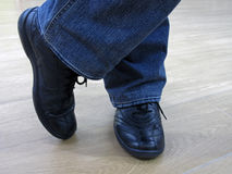 Man stands in jeans and in casual shoes. Man in jeans and everyday shoes. Man in jeans and casual shoes. Male legs in jeans and boots Royalty Free Stock Image