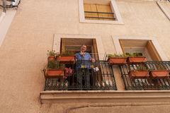 Man stands looking down from balcony surrounded by terracotta fl Stock Photography