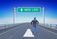 Man stands on a motorway in front of road sign with text New Life stock photography