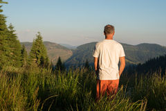 Man stands on a mountain meadow Royalty Free Stock Photography