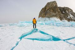 Man stands near cape Khoboy rock on Olkhon Island, Lake Baikal, ice hummocks in winter, Russia, Siberia