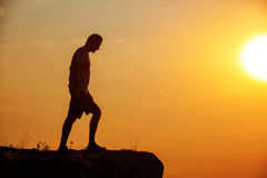 Man stands near the cross on top of mountain Royalty Free Stock Images