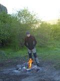 A man stands near a fire. Stock Photos