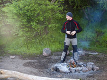 A man stands near a fire. Royalty Free Stock Photo