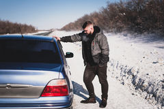 Man stands near his broken car in winter. Man stands near his broken car day Stock Photo