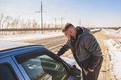 Man stands near his broken car in winter. Man stands near his broken car day Stock Image