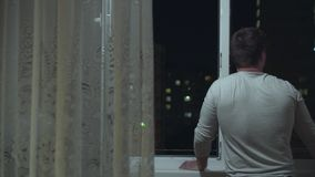 A man stands near an open window and looks at the city lights. Outside the window night city. The concept of freedom and enjoyment. Horizontal camera movement stock video