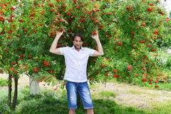 Man stands near the rowan Royalty Free Stock Images