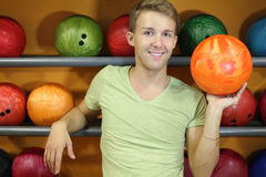 Man stands near shelves with balls in bowling club Royalty Free Stock Photos