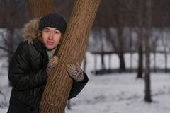 Man stands near the tree in winter park Royalty Free Stock Photo