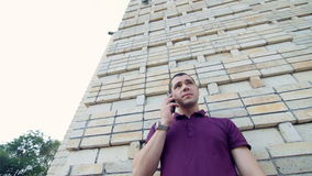 Man stands near a wall, waiting for his girlfriend - said by mobile phone.  stock video