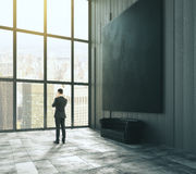 Man stands near a window in a dark room with a blank a picture f stock images