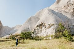 The man stands next to the beautiful rocks and admires the scenery in Cappadocia in Turkey. The landscape of Cappadocia.  Stock Photography