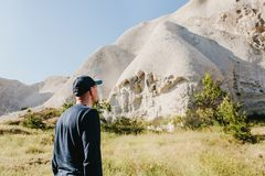 The man stands next to the beautiful rocks and admires the scenery in Cappadocia in Turkey. The landscape of Cappadocia.  Royalty Free Stock Photo