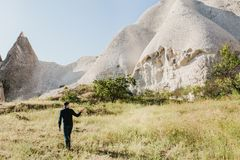The man stands next to the beautiful rocks and admires the scenery in Cappadocia in Turkey and points to one of the. A man stands next to beautiful rocks and Royalty Free Stock Image