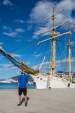 Man stands at the nose of a ship. On the pier Royalty Free Stock Photography