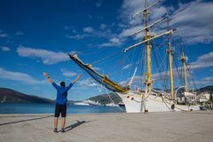 Man stands at the nose of a ship. On the pier Stock Photography