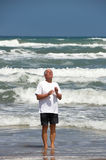 Man stands in ocean, praying. Senior man standing in the ocean, hands raised in prayer, looking into the sun Royalty Free Stock Photography