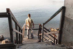 Man stands on old wooden stairway Stock Photography