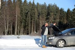 Man stands outdoor near broken car. A man stands in front of a broken car in the winter Royalty Free Stock Image
