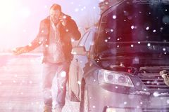 Man stands outdoor near broken car. A man stands in front of a broken car in the winter Stock Images