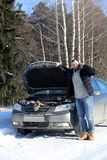 Man stands outdoor near broken car. A man stands in front of a broken car in the winter Royalty Free Stock Photo